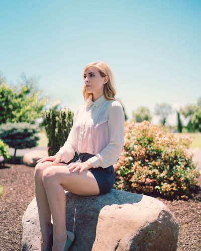 Young Woman Sitting On Rock Against Clear Sky