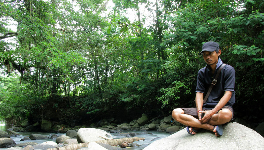 Man sitting on rock at forest