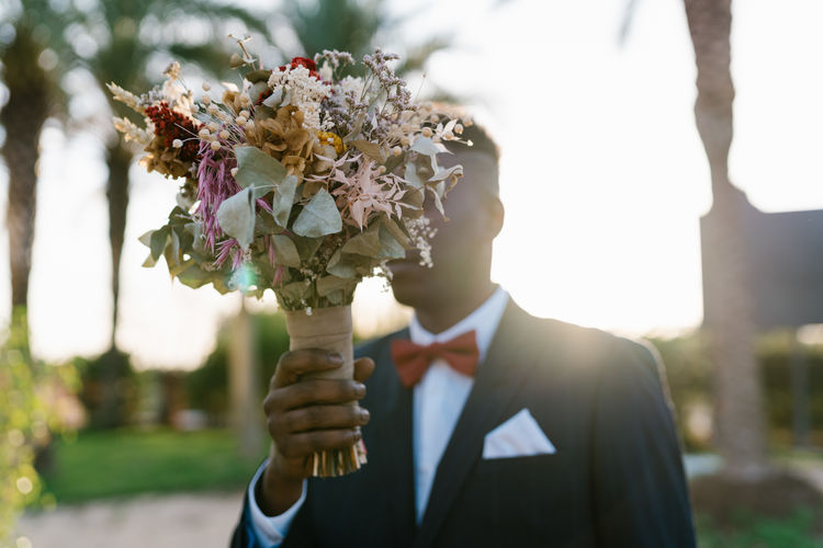 Low angle view of man holding flowering plant