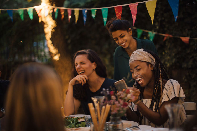 Cheerful multi-ethnic friends enjoying at table during dinner party in backyard