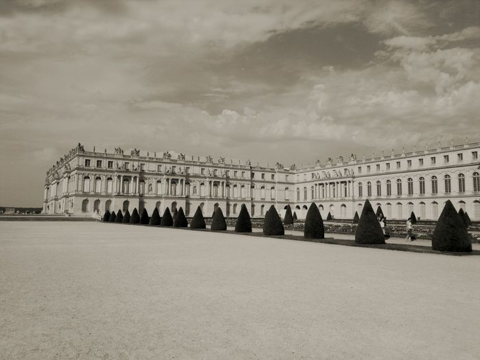 Palace Of Versailles By Garden Against Cloudy Sky
