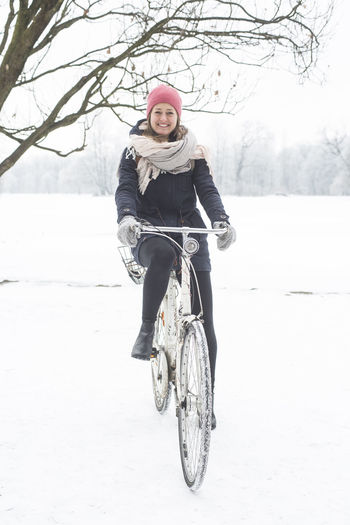 A young lady wrapped up warm in winter clothes poses for the camera whilst sitting on her Amsterdam style bike in the English garden in Munich Winter One Person Full Length Cold Temperature Snow Lifestyles Real People Warm Clothing Leisure Activity Front View Tree Clothing Young Adult Looking At Camera Transportation Portrait Smiling Bicycle Scarf Outdoors Riding Teenager Seehund Englischergarten München