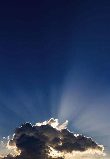 Cumulus of clouds over a mountain in backlight with the rays of the sunset sun marked in the sky