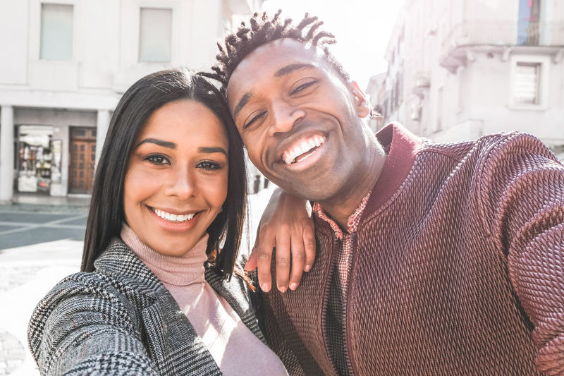 Latin couple taking selfie photo for social network story - Influencers people having fun with new trend technology - Love, fashion and relationship concept - Focus on faces Smiling Happiness Two People Portrait Looking At Camera Young Women Young Men Couple - Relationship Love Outdoors Togetherness Selfie Black African Latin