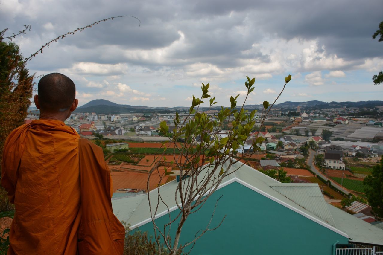 Rear View Of Monk Standing Against Cloudy Sky