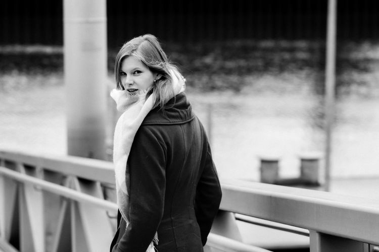 Portrait of beautiful woman standing by railing