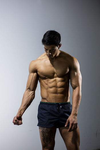 Male fitness model with his head down flexing his arm muscles. Medium shot. Adult Asian  Athlete Body & Fitness Human Body Man Nam Vo Shirtless Sportsman Biceps Fitness Model Flexing Forearm Grey Wall Handsome Head Down Hunk Looking Away From Camera Male Muscle Muscular Build One Person Studio Shot Tatoo Torso