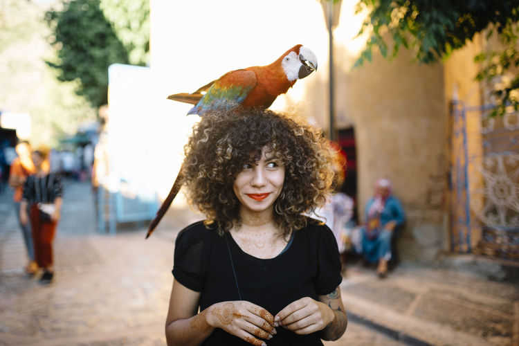 Smiling woman with macaw on head at street