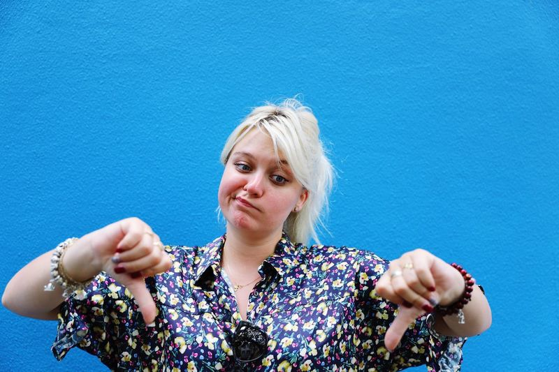 Woman gesturing thumbs down against blue wall