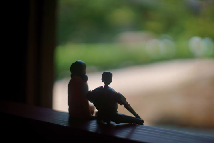 Close-up of figurines on window sill