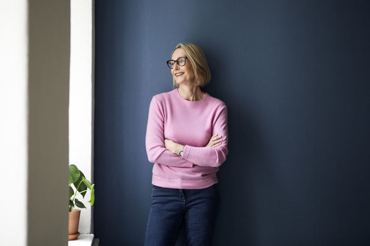 Mid adult woman standing against wall