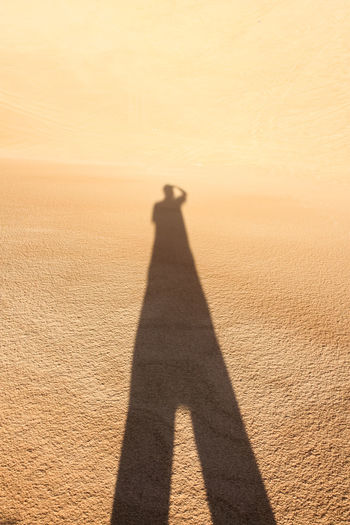 Shadow of man on sand in desert