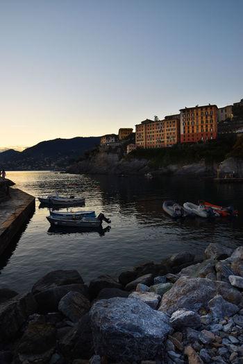 Sailboats moored on sea against clear sky at dusk