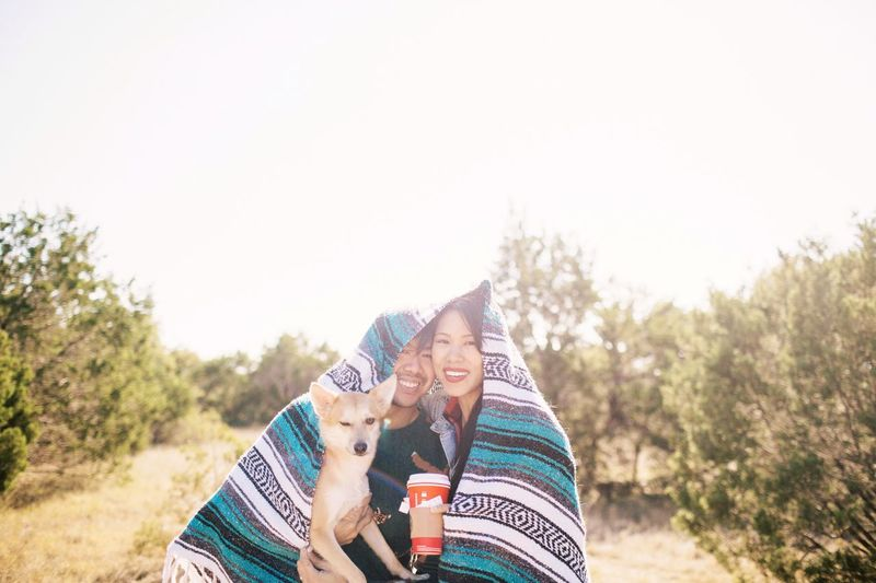 Portrait of couple with dog wrapped in blanket against trees against clear sky
