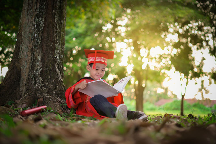 A Boy In A Convocation Graduation Robe Jubah Reading A Book In Beautiful Garden Background Beauty In Nature Boy Child Childhood Children Only Convo Convocation Day Forest Full Length Graduation Graduation Ceremony Kids Convocat Kindergarten Motarboard Nature One Person Outdoors People Sitting Tree Great Outdoors-EyeEm Awards 2017 The Portraitist - 2017 EyeEm Awards