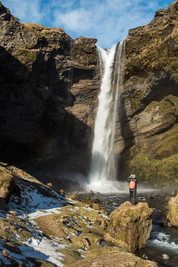 Rear View Of Man Standing On Rock Against Kvernufoss Waterfall