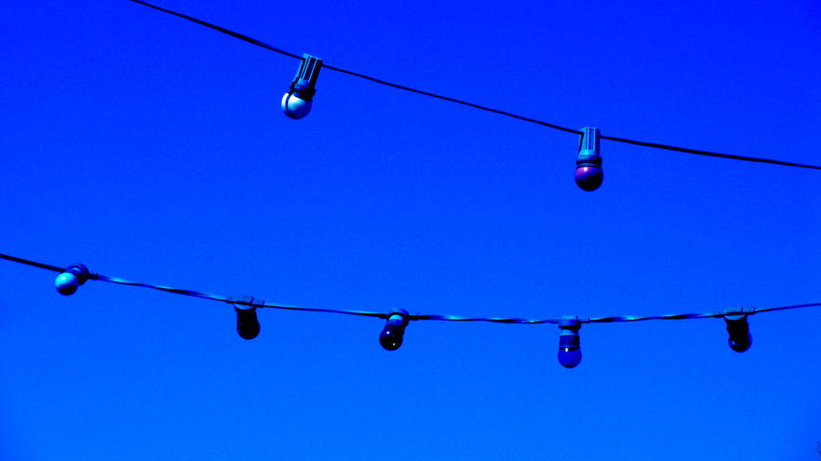 Low Angle View Of Lighting Decorations Hanging Against Clear Blue Sky