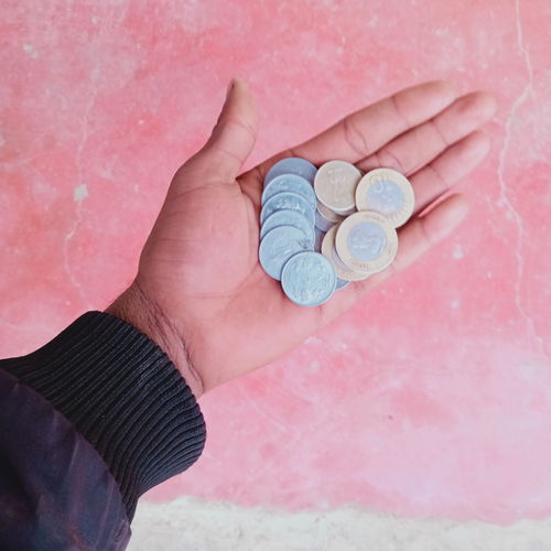 High angle view of hand holding coins against wall