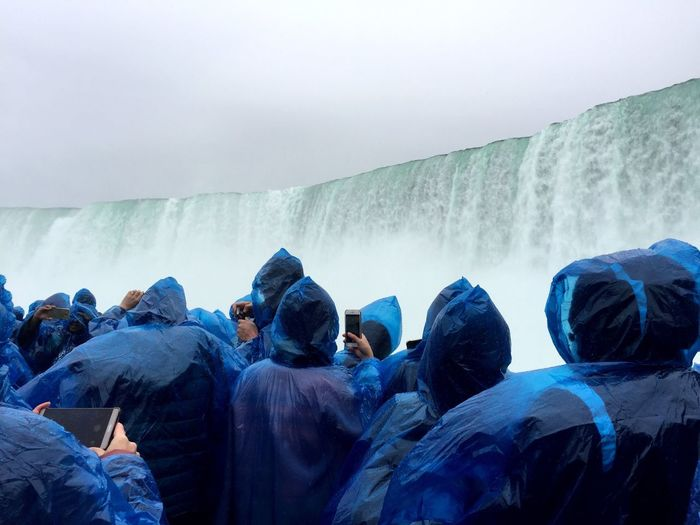 Rear view of tourists in blue raincoats against niagara falls