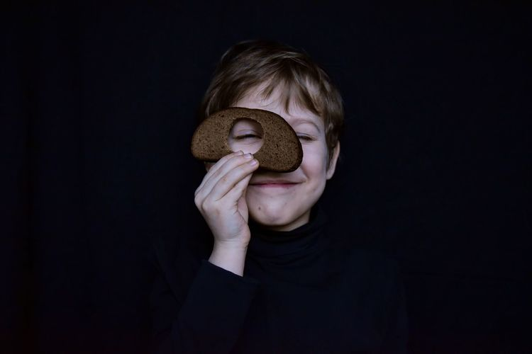 Close-up of boy holding bread against black background