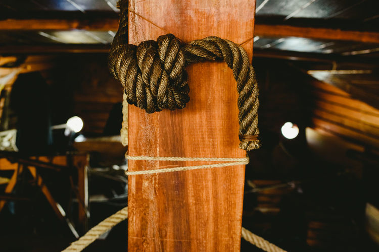 Close-up of rope tied up on wood