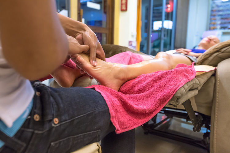Close-Up Of Woman Getting Foot Massage At Salon