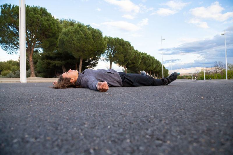 Surface level of man sleeping on road in city against sky