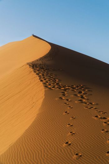 Footprints on sand dune in desert against clear sky