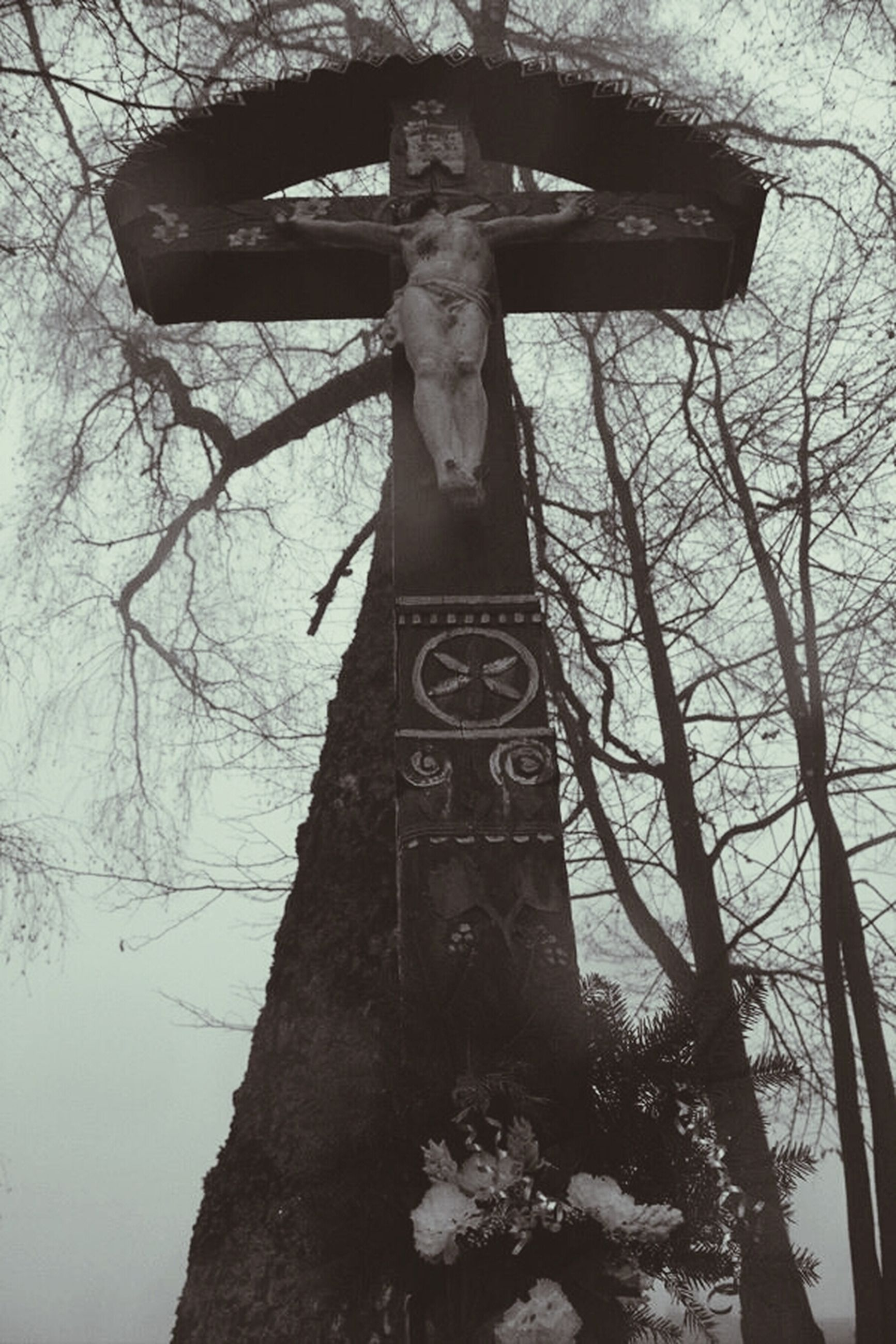 text, tree, human representation, low angle view, communication, western script, art, art and craft, creativity, old, outdoors, day, no people, sky, religion, built structure, abandoned, cross, bare tree