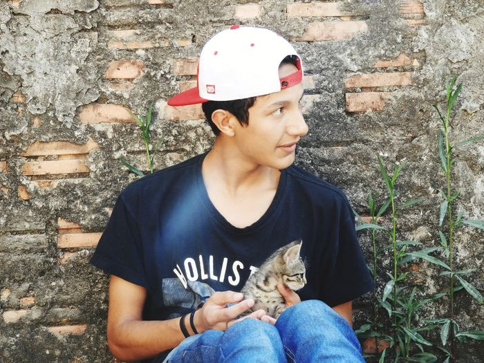 Teenage boy with cat looking away while sitting against wall