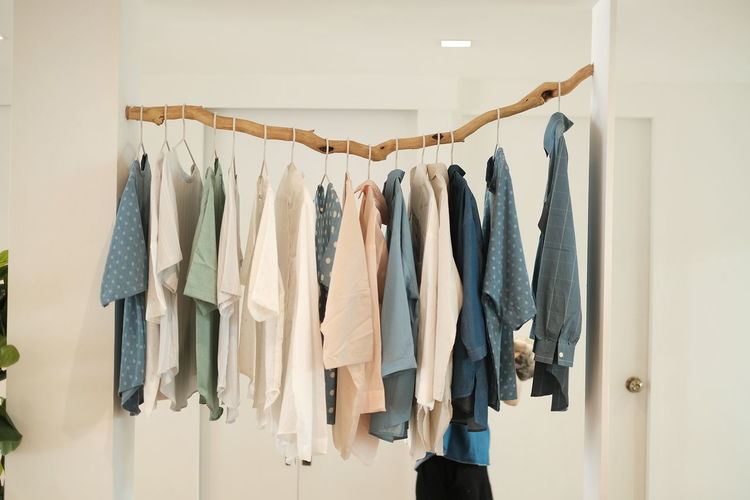 Row of clothes hanging on wall at home