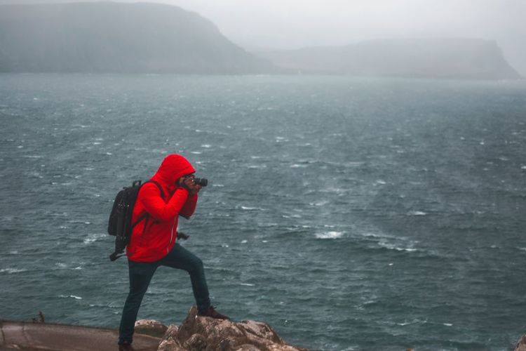 Man in sea against mountain