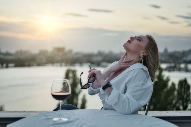 Side view of young woman holding drink against sky at sunset