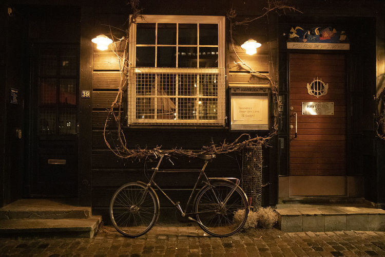 Bicycle parked on street against building at night