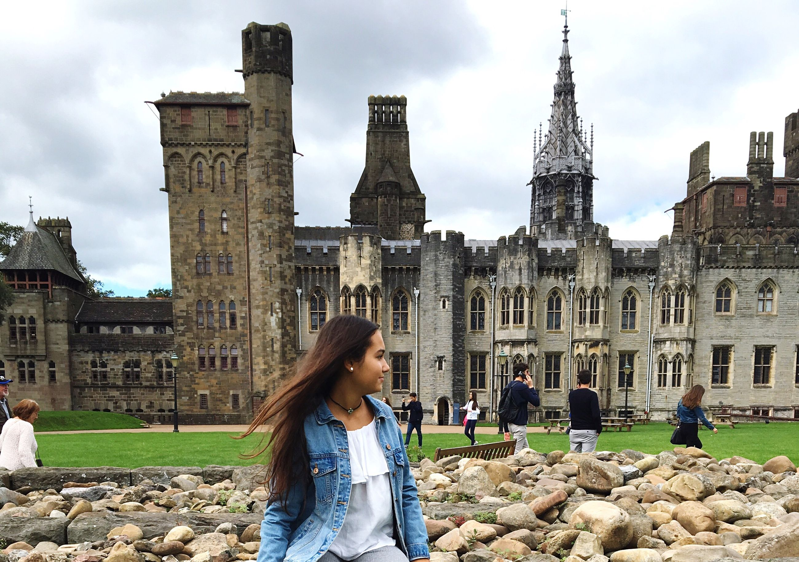 architecture, building exterior, built structure, in front of, side view, famous place, travel destinations, long hair, city, national landmark, cloud - sky, tourism, sky, casual clothing, outdoors, history, stone material, city life, day, gesturing, memories, the past, person
