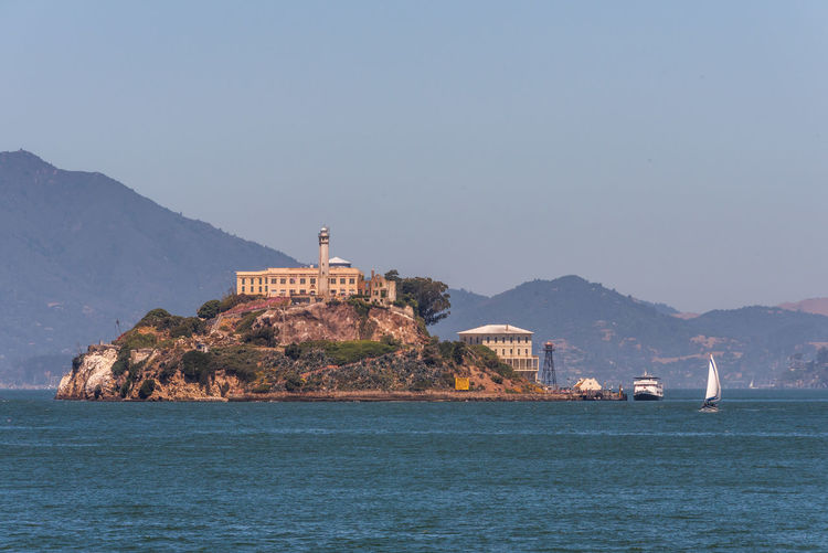 Alcatraz Prison Water Sea Mountain Architecture Sky Built Structure Building Exterior Waterfront Nature Building No People Copy Space Scenics - Nature Clear Sky Travel Destinations Land Nautical Vessel Day Mountain Range Lighthouse Guidance Outdoors
