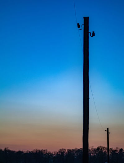 Low angle view of silhouette pole against clear sky during sunset