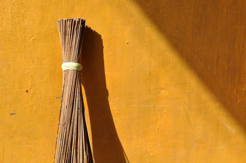 broom stick Wall - Building Feature Yellow No People Shadow Close-up Wood - Material Sunlight Day Indoors  Still Life Brown Built Structure Architecture Single Object Cleaning Nature Musical Instrument Broom