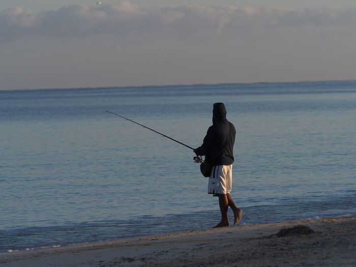 Side view of man fishing while standing at beach against sky during sunset