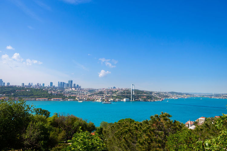 Scenic view of city by sea against blue sky