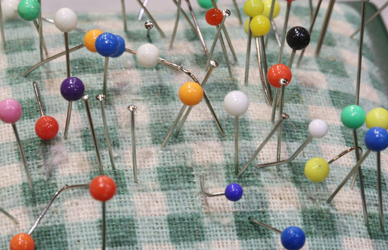 colored pins for sewing stuck on a pincushion in a haberdashery Pins Tailor Tailoring Backdrop Backgrounds Choice Close-up Decoration Large Group Of Objects Macro Multi Colored Needle Needles Pin Pin Cushion Pincushion Still Life Straight Pin Thread