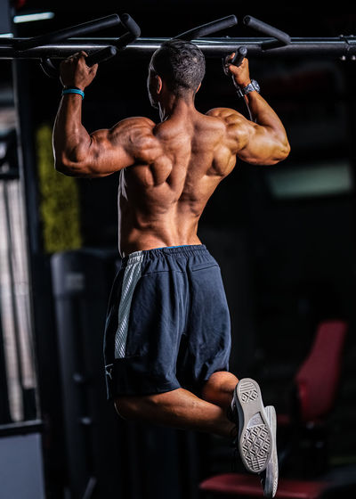Full length rear view of shirtless man exercising with equipment in gym