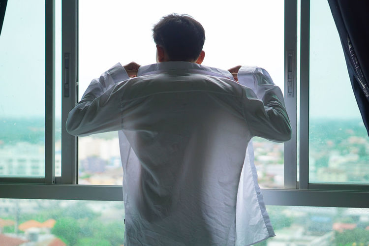 Rear view of a man looking through window