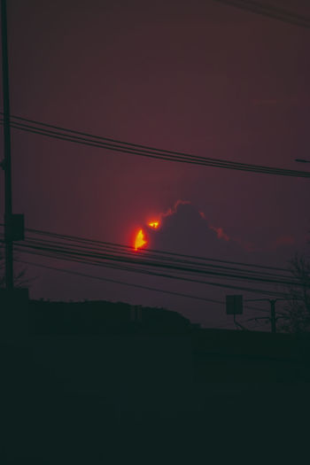 Silhouette of power lines against sky during sunset