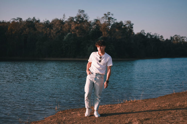 Young man standing by lake against sky