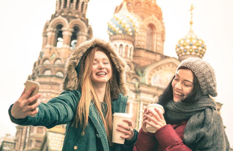 Cheerful friends taking selfie against church