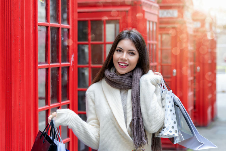 Portrait of an attractive London shopping woman with shopping bags in her hand Smiling Young Adult Portrait Looking At Camera Happiness One Person Standing Front View Women Consumerism Positive Emotion Scarf Beautiful Woman Beauty Emotion London Telephone Booth Shopping Bags Concept Sun United Kingdom Sales Travel Red
