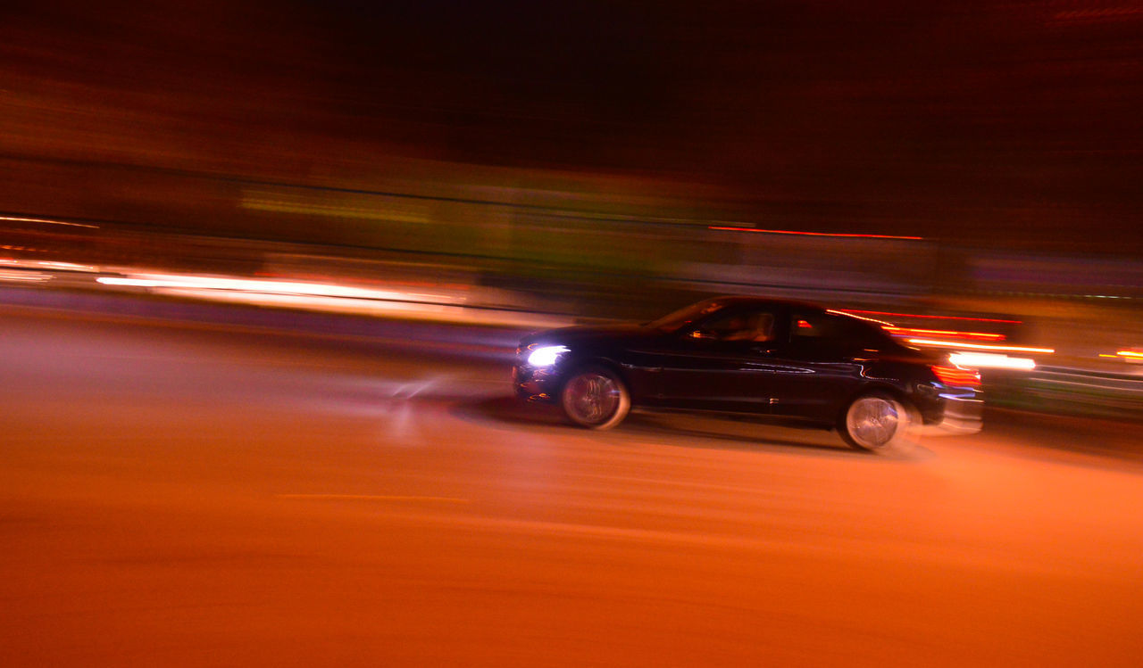 mode of transportation, speed, blurred motion, transportation, motion, illuminated, land vehicle, car, motor vehicle, on the move, city, night, no people, long exposure, road, street, travel, outdoors, architecture, orange color