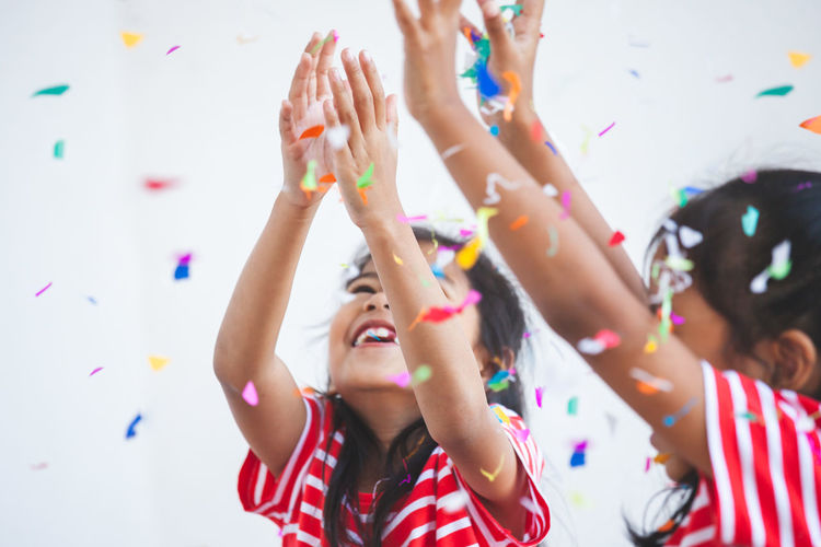 Cheerful sisters with confetti against white background