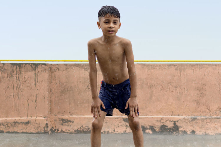 One skinny wet boy playing and having fun in rain at his terrace, outdoors during monsoon season.